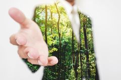 Dubbel exponering, affärsman som sträcker handen till handskakan med gröna träd i den skogEco vänskapsmatchen och den hållbara af fotografering för bildbyråer