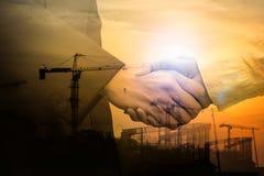 dubbel exponering Affärsmanhandskakning på industriell bakgrund royaltyfri fotografi