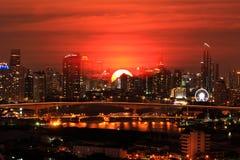 Dubbel exponering av över nattplatsstaden på härlig solnedgångbakgrund, varm begreppsvärld royaltyfri bild