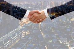 Dubbel exponering av affärsmanhandskakningöverenskommelse med citysca arkivbilder