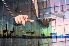 Dubbel exponering av affärsmannen med den Digital minnestavlan och port Carg arkivbilder