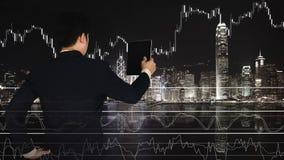 Dubbel exponering av affärsmannen som använder minnestavlan med den finansiella grafen fotografering för bildbyråer