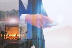 Dubbel exponering av den hållande minnestavlan för affärsman med stads- bakgrund arkivbild
