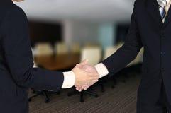 Dubbel exponering av den säkra asiatiska affärsmannen som skakar handen i mötesrum royaltyfri foto