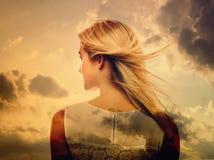 Dubbel exponering av den unga kvinnan och himlen royaltyfri bild