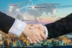 Dubbel exponering av en affärsmanhandskakning med den globala delen för översikt Arkivbild