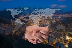 Dubbel exponering av en affärsmanhandskakning på världen globala Carto arkivfoton
