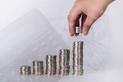 Dubbel exponering av handen satte pengarmynt till bunten av mynt och bl arkivfoto
