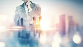 Dubbel exponering av staden och affärsmannen med ljusa effekter Arkivbild