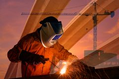 Dubbel exponering av strukturen för arbetarsvetsningstål med den industriella kranen Royaltyfri Foto