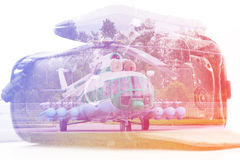 Dubbel exponering: bärande fall för kameran och en helikopter Affärs-, press-, resque- och loppbegrepp Royaltyfri Bild