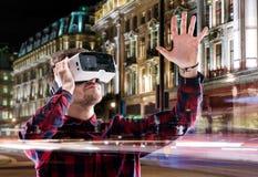 Dubbel exponering, bärande virtuell verklighet för man rullar med ögonen, nattstaden Royaltyfria Bilder