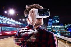 Dubbel exponering, bärande virtuell verklighet för man rullar med ögonen, nattstaden Arkivbilder