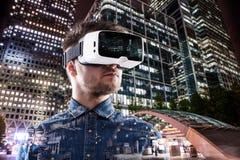 Dubbel exponering, bärande virtuell verklighet för man rullar med ögonen, nattstaden Royaltyfri Bild