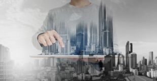 Dubbel exponering, en man som använder den digitala minnestavlan och modernt byggnadshologram Fastighetaffär och begrepp för bygg Arkivbilder