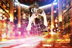 Dubbel exponering, unga flickan som får hörlurar med mikrofon för erfarenhet VR, använder ökade verklighetexponeringsglas och att Arkivfoton
