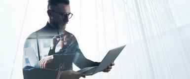 Dubbel exponering uppsökte affärsmannen som bär den svarta skjortan och exponeringsglas, hållande moderna anteckningsbokhänder St Arkivfoto