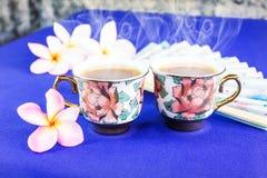 Dubbel kopp te i älskvärda koppar för kortkort för blommamodell Arkivfoto