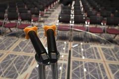 Dubbel mikrofon på en tabell för exponeringsglasrundasida på konferenskorridoren royaltyfria bilder