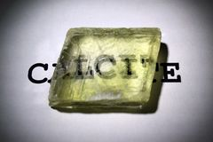 Dubbel refraktion av text i kristall för Island mast Calciteprov med optisk dubbelbrytning royaltyfri foto