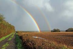Dubbel regnbåge över äng Arkivfoto