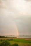 Dubbel regnbåge över en sjö Arkivfoto