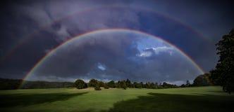 Dubbel regnbåge över gröna fält Arkivfoto