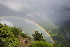 Dubbel regnbåge över kullar Arkivbilder