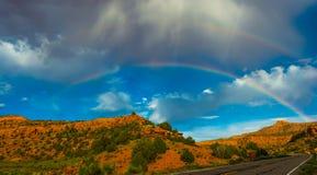 Dubbel regnbåge över vägen Royaltyfria Bilder