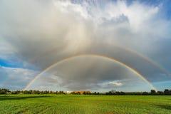 Dubbel regnbåge efter enorm storm Arkivbild