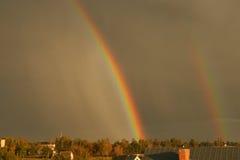 Dubbel regnbåge efter storm Arkivfoto