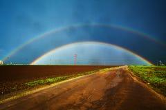 Dubbel regnbåge och väg Arkivfoton