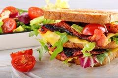 Dubbel smörgås med baconost och grönsaker på träbackg Royaltyfri Foto
