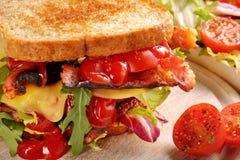 Dubbel smörgås med baconost och grönsaker på träbackg Arkivbild