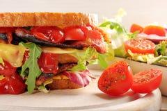 Dubbel smörgås med baconost och grönsallat Royaltyfri Foto
