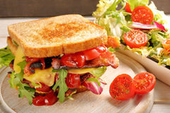 Dubbel smörgås med baconost och grönsallat Arkivfoto