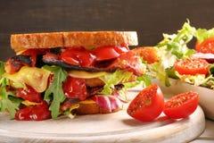 Dubbel smörgås med baconost och grönsallat Royaltyfri Fotografi