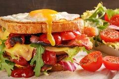 Dubbel smörgås med det baconost och ägget på träbakgrund Royaltyfri Bild