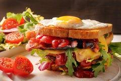 Dubbel smörgås med det baconost och ägget på träbakgrund Arkivbild