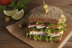 Dubbel smörgås med skinka, ost, grönsallat, tomaten och gröna oliv helt brödkorn Mellanmål eller bort mat för tagande Svart bakgr arkivfoto