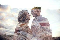 Dubbel van de blootstellingsman en vrouw paar die met bergen op achtergrond koesteren Bergen binnen paar in liefde De minnaars be royalty-vrije stock afbeelding