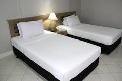 Dubbel vit madrass och svart säng royaltyfria bilder