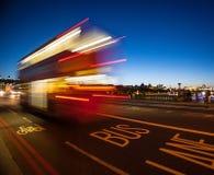 Dubbeldekkerbus die de Brug van Westminster kruisen bij nacht Royalty-vrije Stock Afbeeldingen