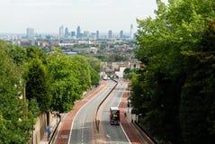 Dubbeldekkerbus op een weg met de horizon van Londen op de achtergrond Stock Foto's