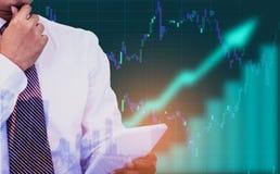 Dubbele blootstelling - de zakenman die een tablet in hand houden, achtergrond is een van de pijlteken en voorraad grafieken en p royalty-vrije stock afbeelding