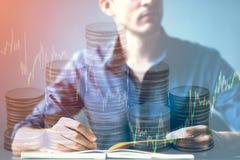 Dubbele blootstelling die van zakenman op bureau en effectenbeurs of forex grafiek en stapelmuntstuk kronkelen geschikt voor fina stock fotografie