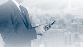 Dubbele blootstelling van de bedrijfsmens met mobiele telefoon en stadsgebouwenachtergrond abstract ontwerpidee Stock Foto's