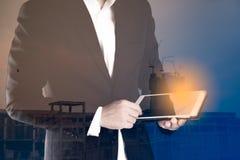 Dubbele blootstelling van een bedrijfsmens die tablet voor onroerende goederen het werken gebruiken Royalty-vrije Stock Afbeelding