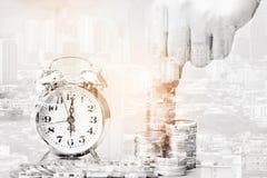Dubbele blootstelling van Hand die geldmuntstukken zetten aan stapel van muntstukken en retro wekker op stadsachtergrond voor Onr royalty-vrije stock foto