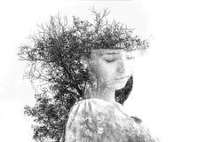 Dubbele blootstelling van jong mooi meisje onder de bladeren en de bomen Portret van aantrekkelijke die dame met foto van boom wo royalty-vrije stock fotografie